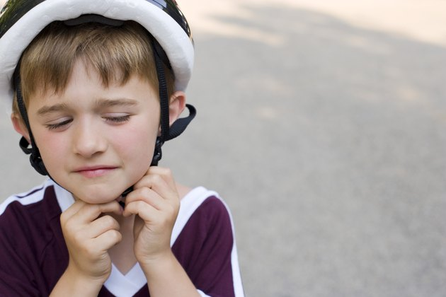 Boy adjusting helmet