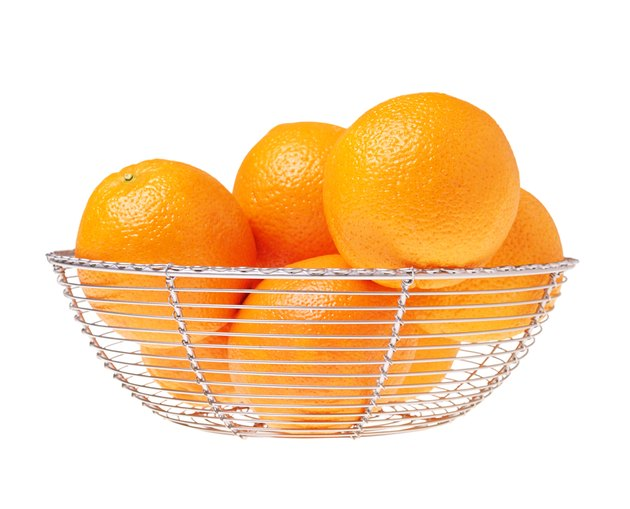 Still life of a glass bowl full of oranges