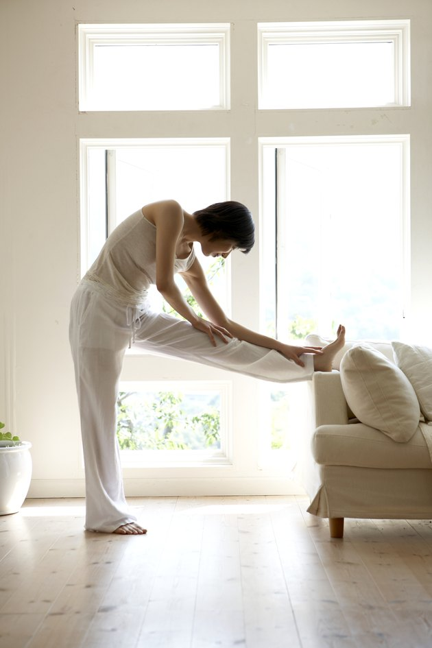Young woman stretching legs on sofa in living room