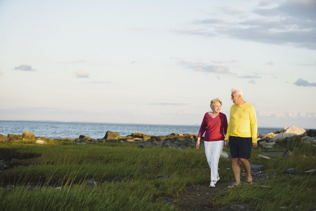 Senior couple walking near ocean