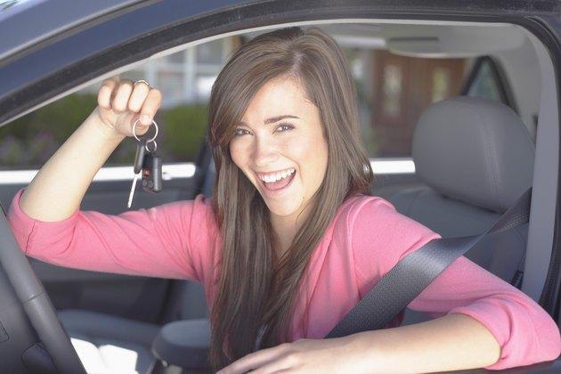 Smiling teenage girl holding keys inside car