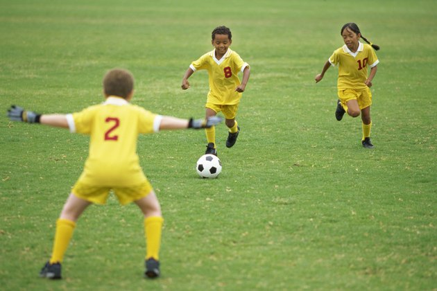 two boys and a girl playing soccer