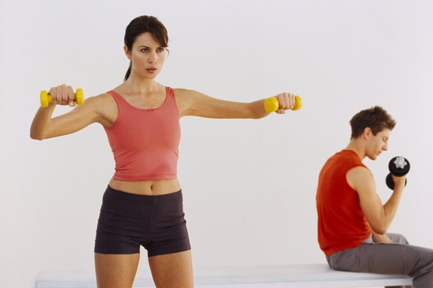View of a young couple working out with dumbbells
