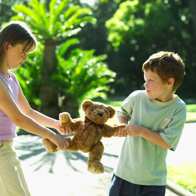 boy and a girl fighting over a teddy bear