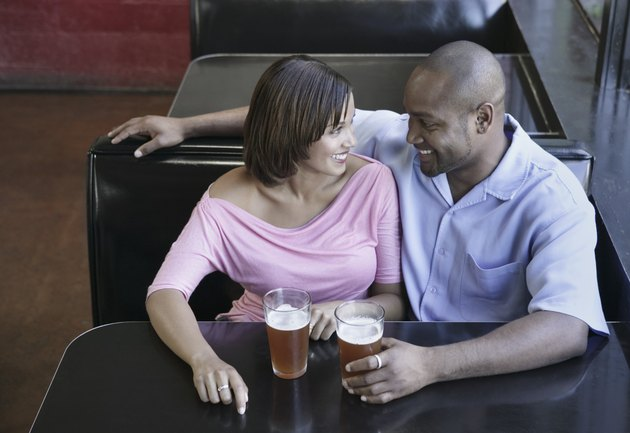 High angle view of a young couple sitting at a restaurant table with a glasses of beer