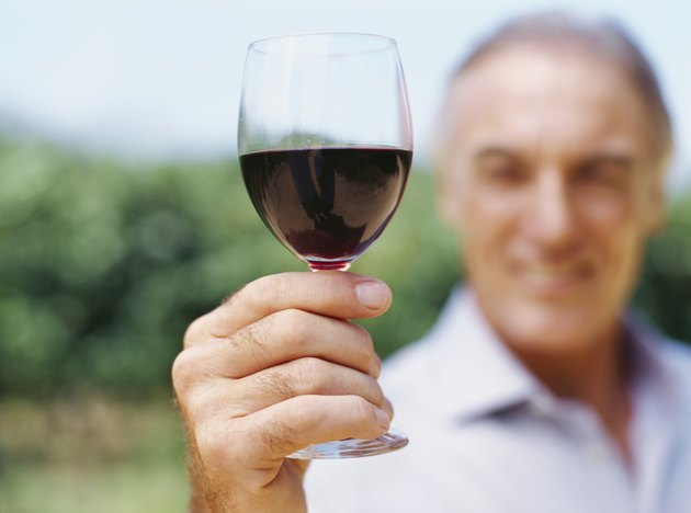 mature man showing a glass of red wine