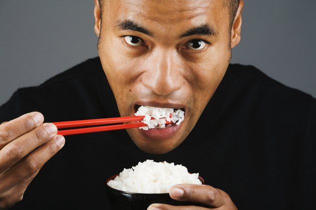 Asian man eating rice with chopsticks
