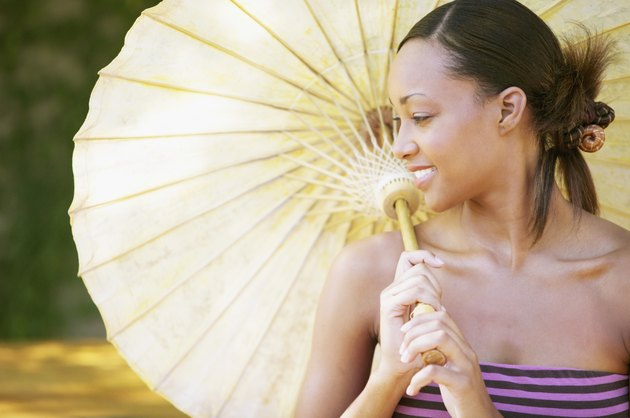 Young woman holding a parasol smiling