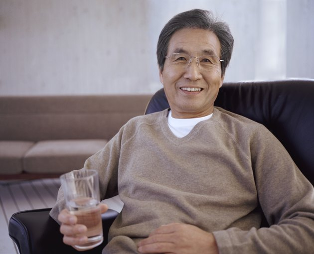 Portrait of a Senior Man Sitting on a Chair Holding a Glass of Water