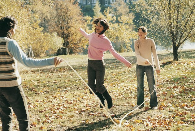 Three Adults Skipping With a Rope in a Park in Autumn