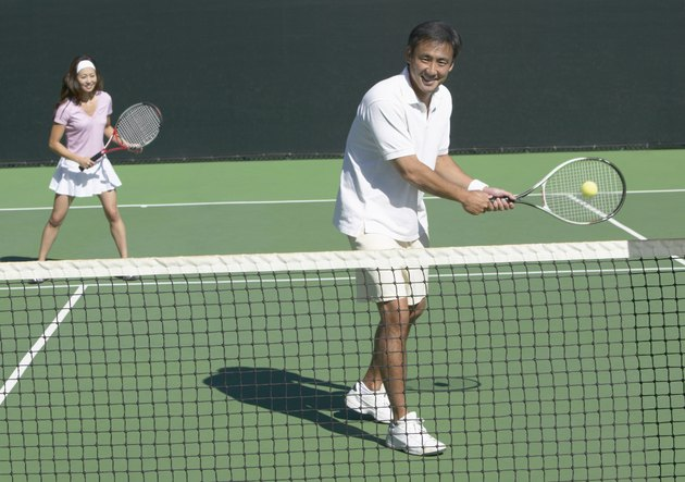 Man and Woman Playing Tennis Together on a Court