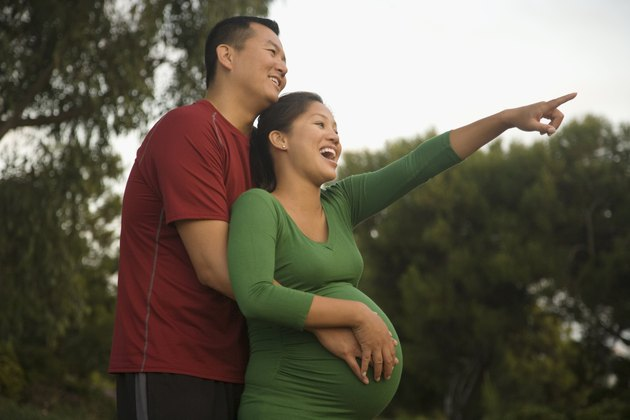 Pregnant Asian couple hugging