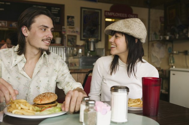 Happy couple in diner together with burger and fries