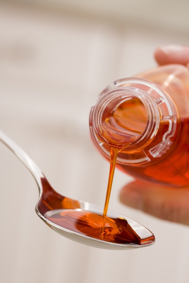 Hand pouring cough syrup into spoon