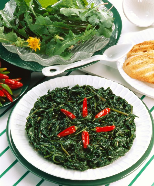 high angle view of a side dish of green garnished with chilies and served with salad and bread