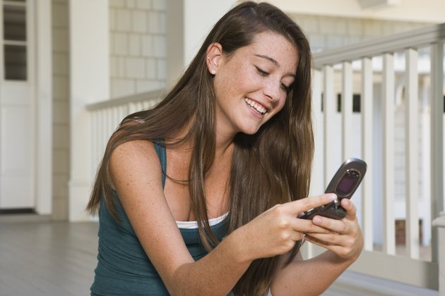 Smiling teenage girl using cell phone