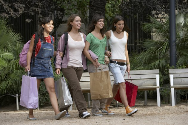 Four teenage girls (15-17) on sidewalk carrying shopping bags