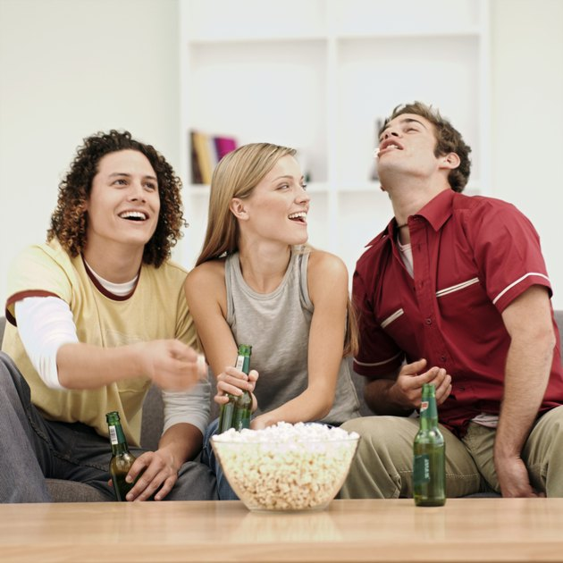 Three young people eating popcorn and drinking beer in room