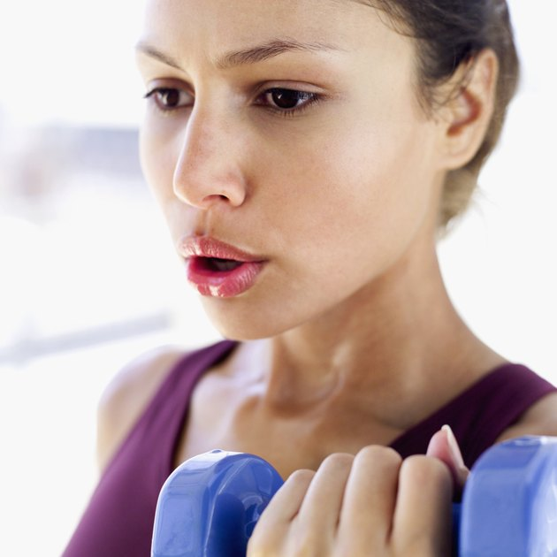 Close-up of a young woman lifting a dumbbell