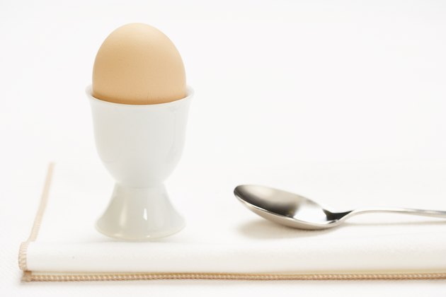 Egg in cup with spoon on cloth napkin