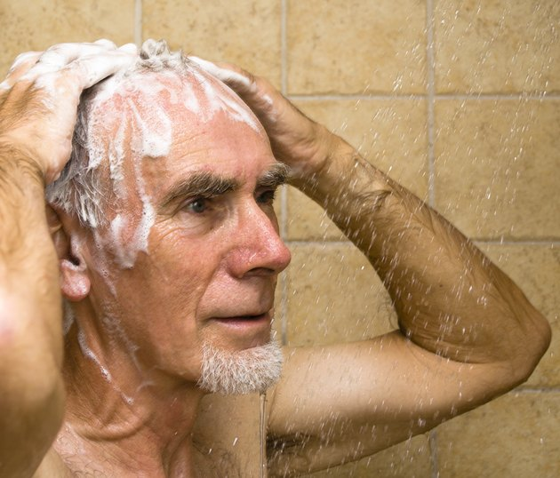 Senior man washing hair in shower