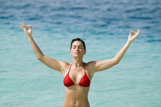Young woman meditating at beach