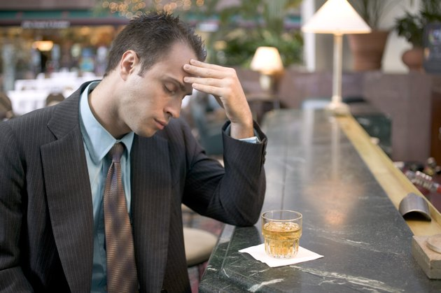 Stressed businessman sitting at bar with drink