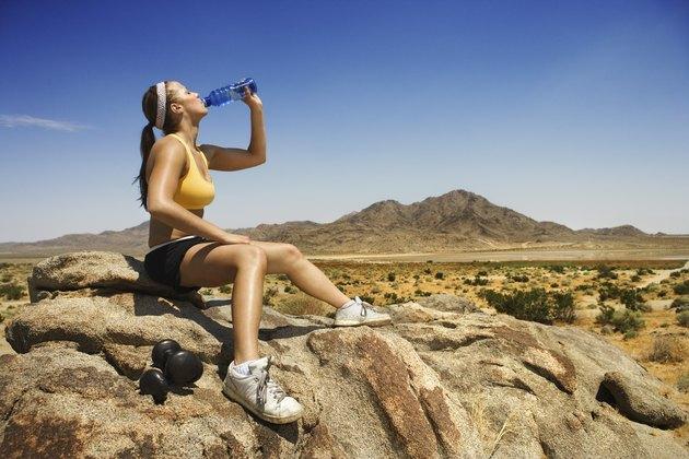 Woman drinking water in desert