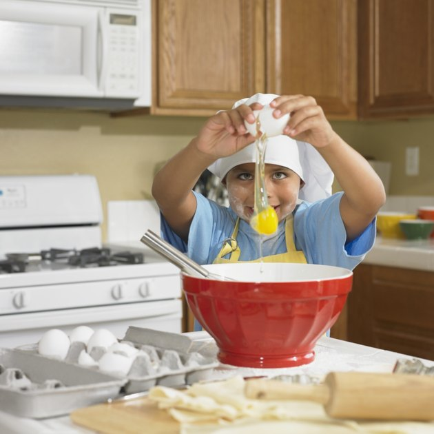 Young Hispanic boy cracking egg into bowl in kitchen