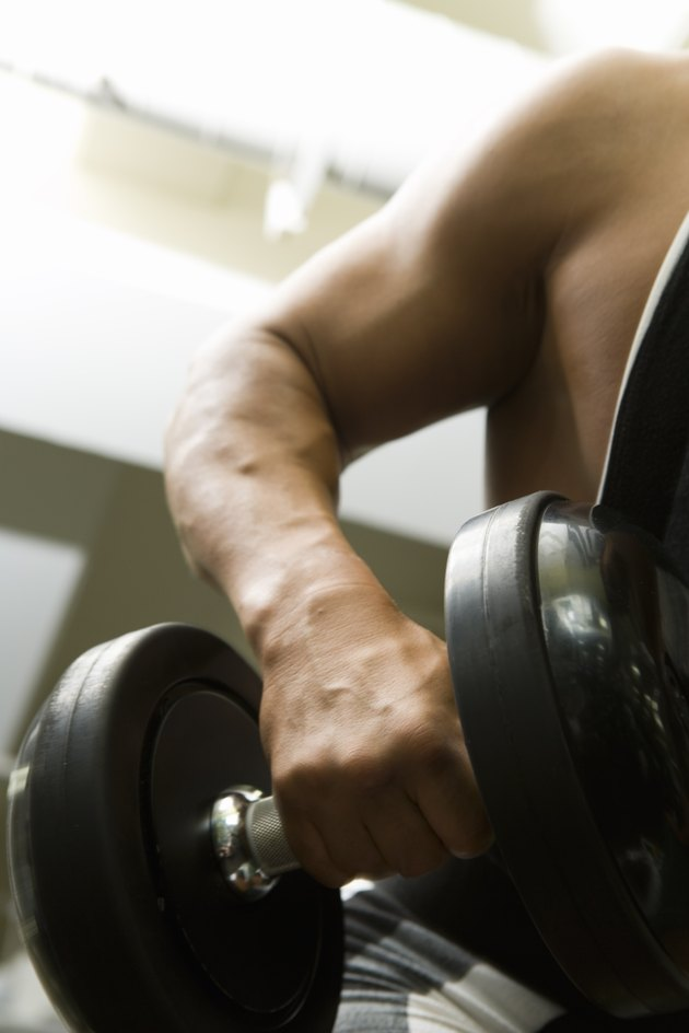 Man lifting dumbbell in gym, front view, differential focus