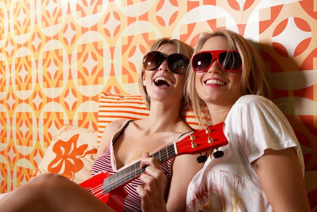 Two young women wearing sunglasses, sitting on bed, one playing guitar, laughing