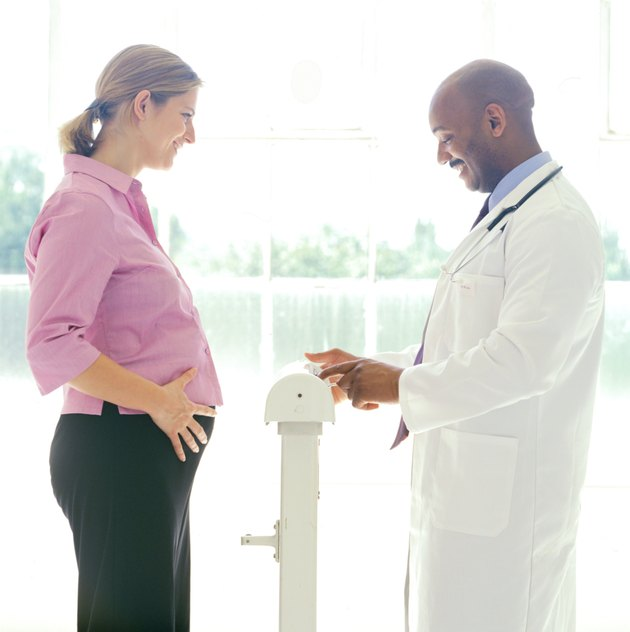 portrait of a young pregnant woman getting her weight checked by a doctor