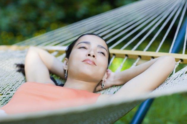 Hispanic woman laying in hammock