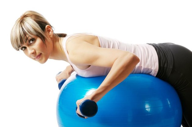 Young beautiful sportswoman exercising on a fitness ball.