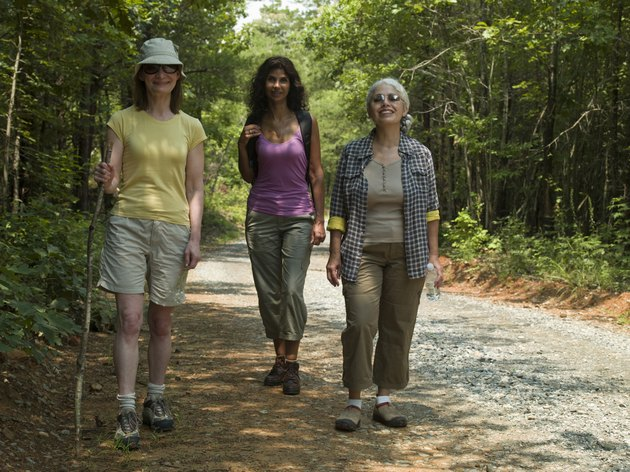 Three mature woman walking road in forest, smiling