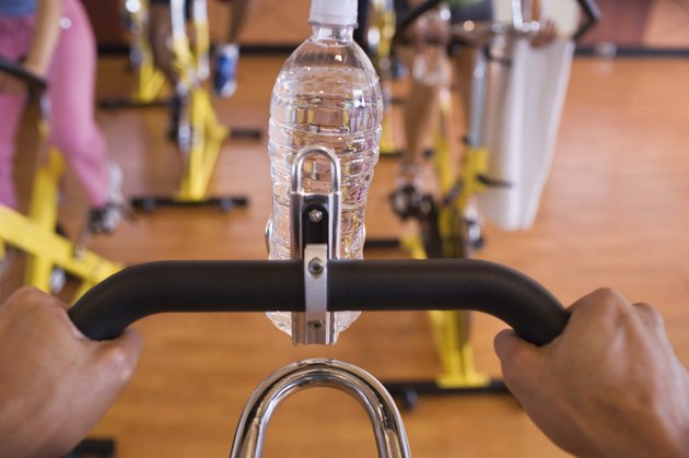 Person holding handlebars with bottled water at gym