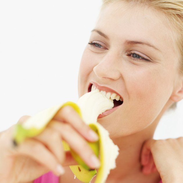 Close-up of a young woman eating a banana