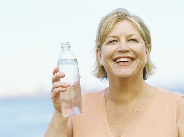 close-up of a mature woman holding a water bottle