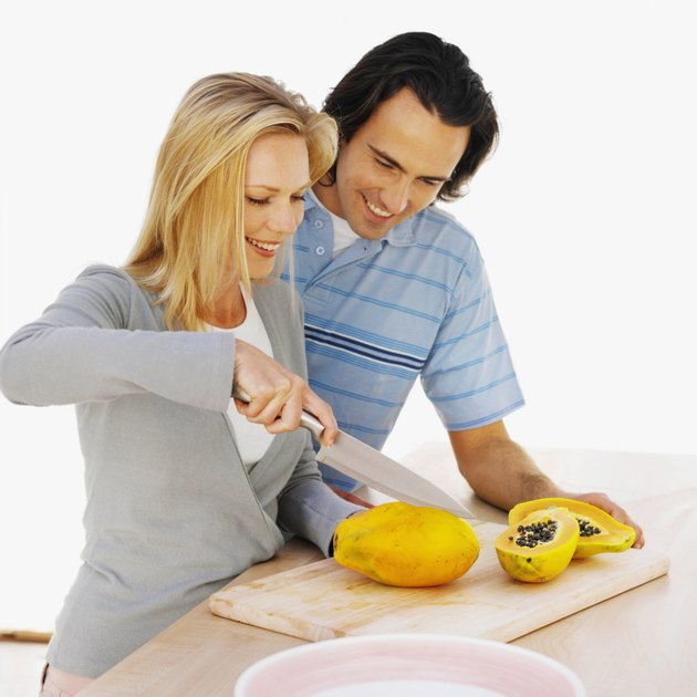 Close up of a young smiling couple cutting fruit on a chopping board