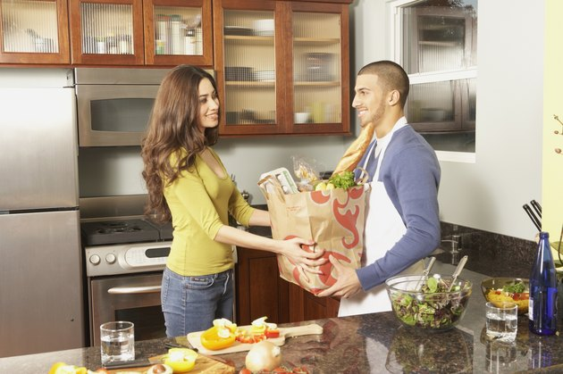 Young Hispanic couple with grocery bag in the kitchen