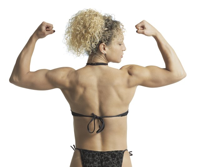 rear view medium shot of an adult female body builder as she flexes her muscles