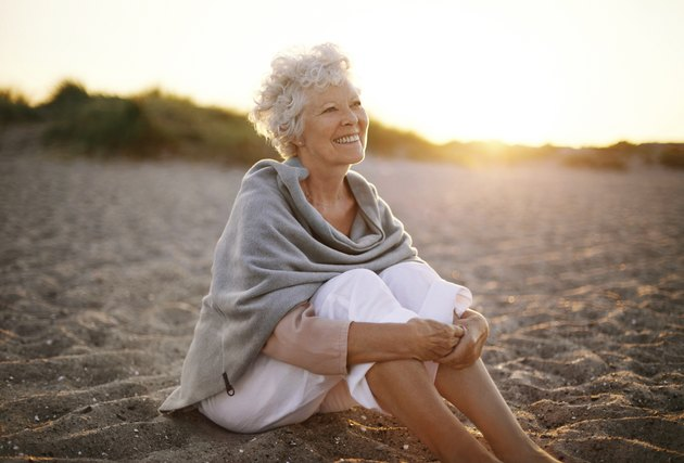 Cheerful old woman sitting on the beach