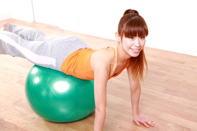 young Japanese woman doing exercise with fitness ball