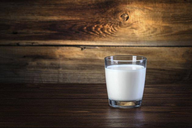glass of milk on wooden background