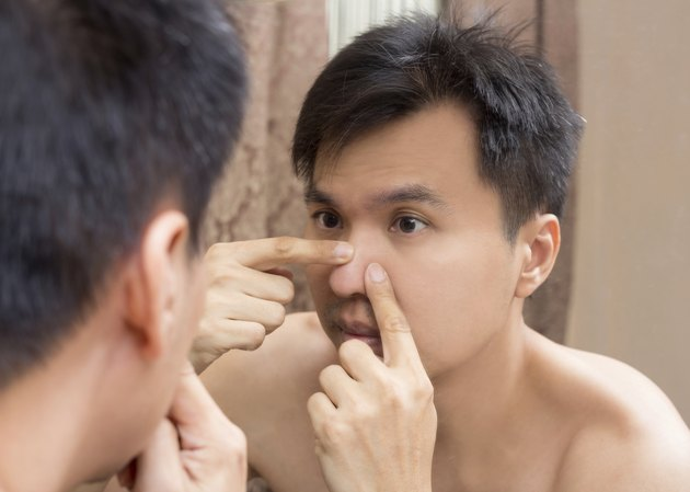 Mirror reflection of asian handsome man viewing his face