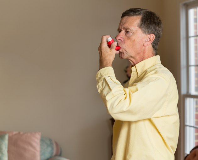 Senior retired man with asthma inhaler