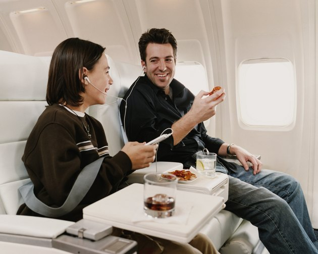 Man Sits in a Plane Seat Next to His Son, Sharing Headphones and Eating a Snack