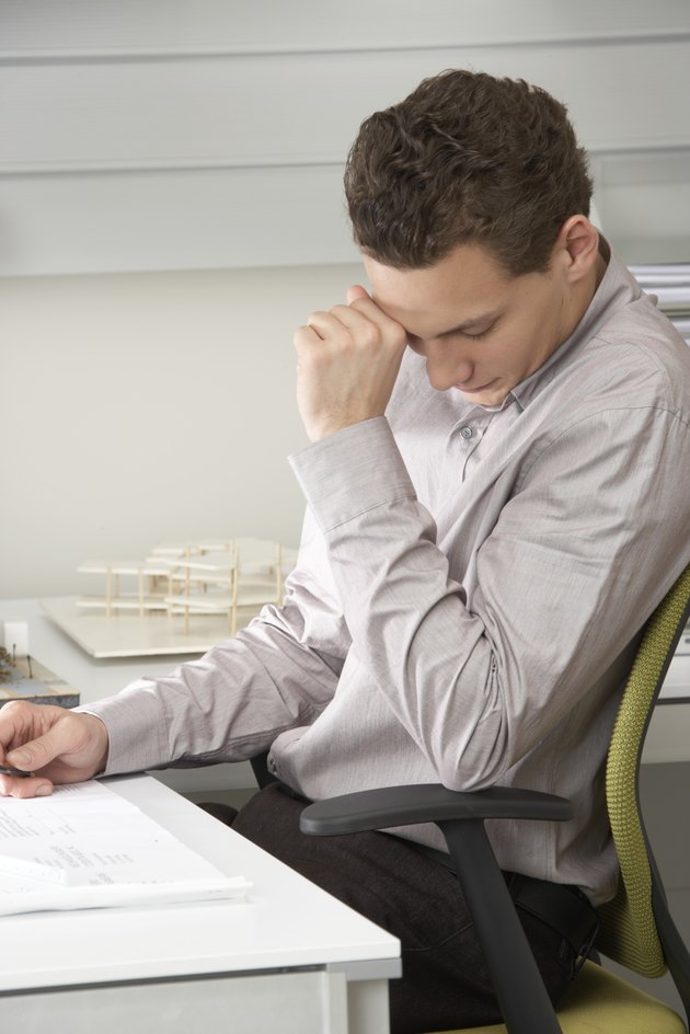 Young businessman at desk, hand by face