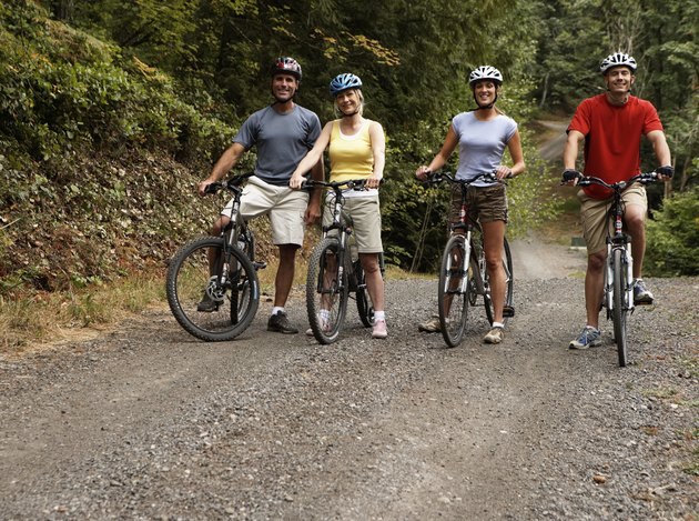 Four adults on mountain bikes on dirt road, portrait
