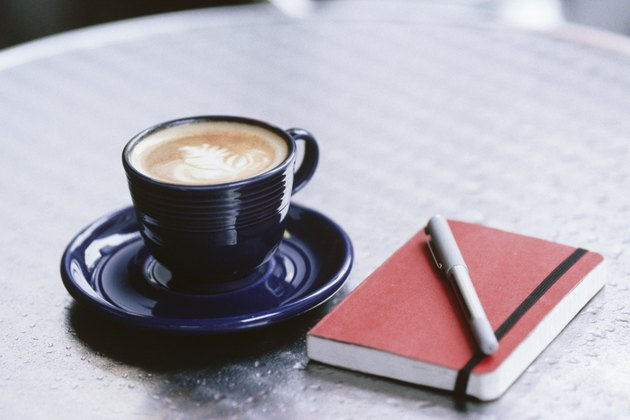 Cup of coffee, notebook and pen lying on table